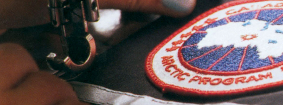 Craftsman stitching Canada Goose logo onto a product